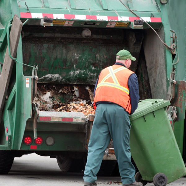 Worker emptying residential waste into a truck