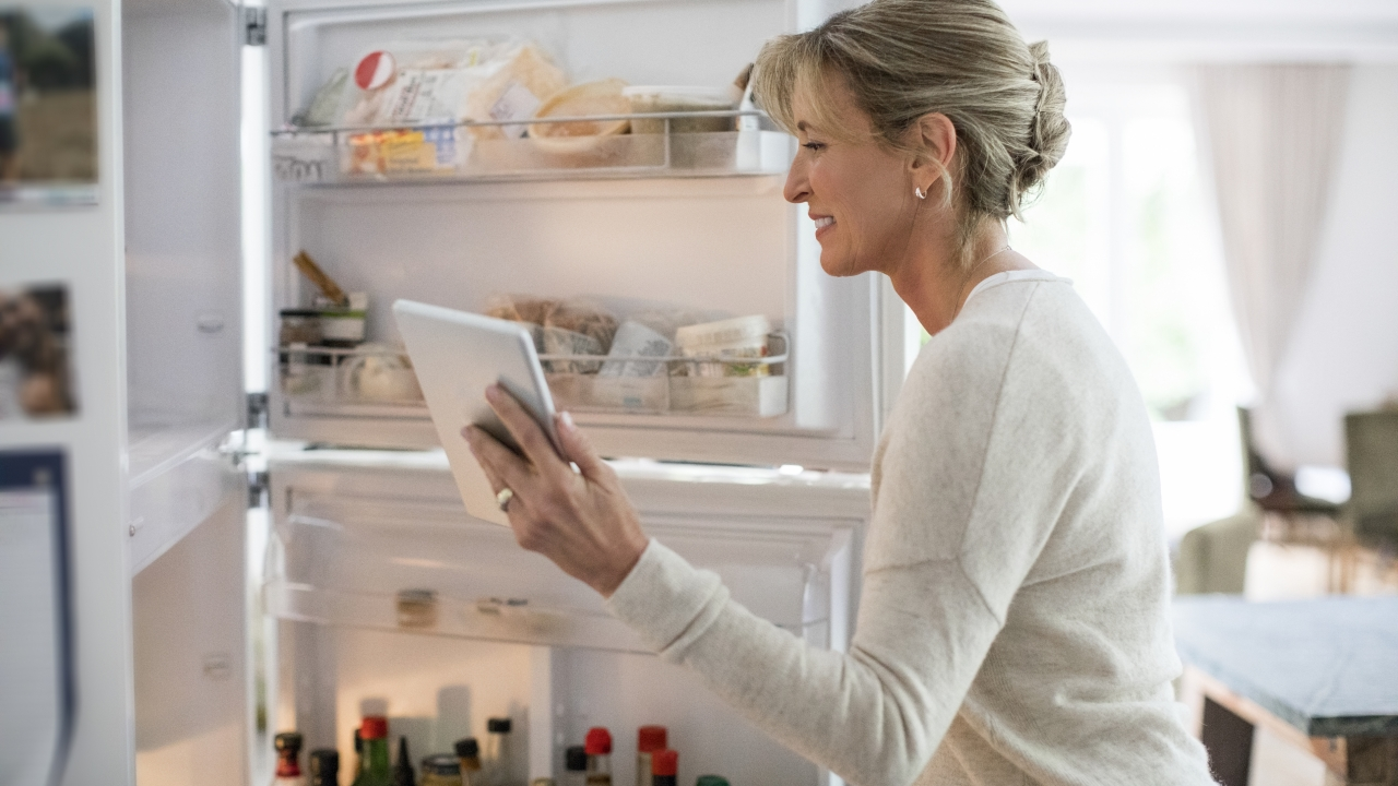 Woman with tablet PC looking into refrigerator