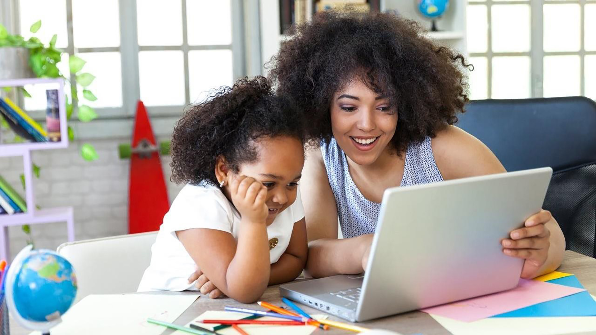 A woman using a laptop with a child