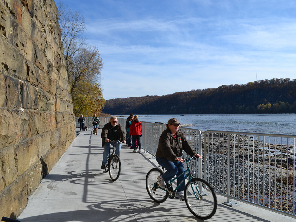 People riding their bikes and walking along a trail beside a river