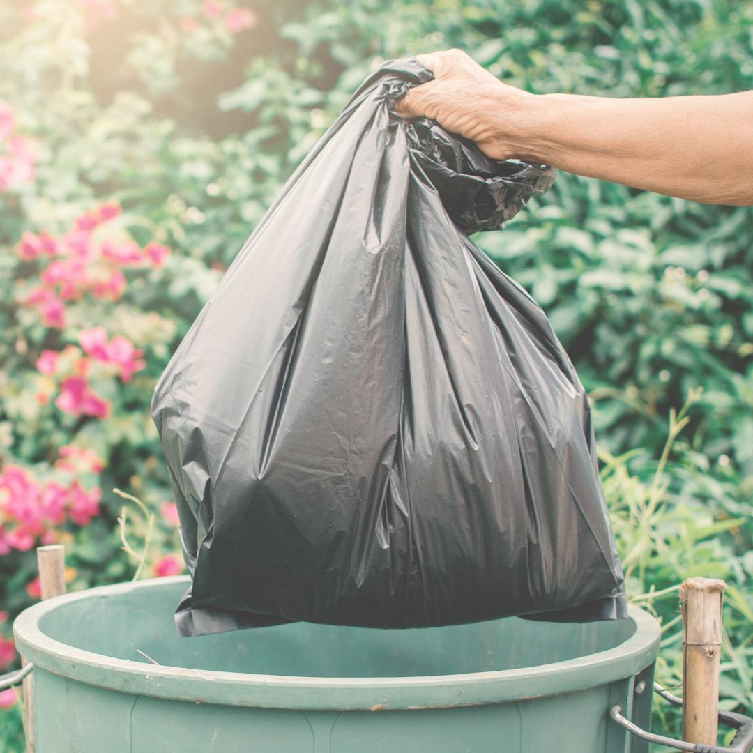 Hand disposing trash bag in a trash bin
